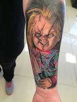 tatuaje para halloween chucky realista a color en el antebrazo