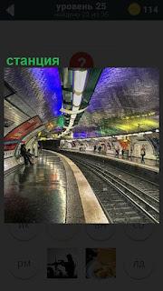 Ярко освещенная станция и красиво расписанная, люди и рельсы