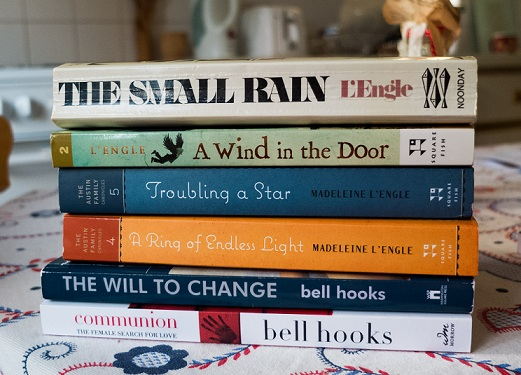 Pile of books: The Small Rain, A Wind at the Door, A Ring of Endless Light and Troubling a Star by Madeline L'Engle and The Will to Change and Communion by bell hooks