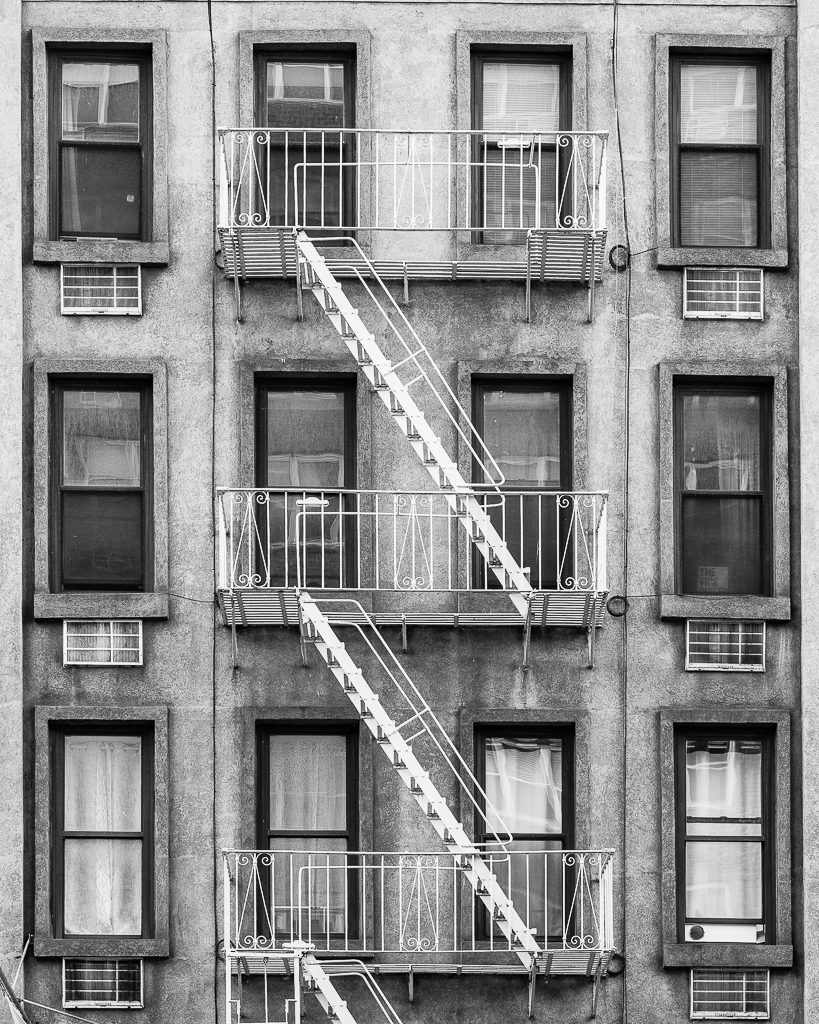 a photo in black and white of an elegant fire escape in new york city