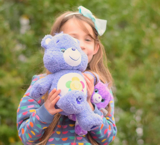 child holding care bear