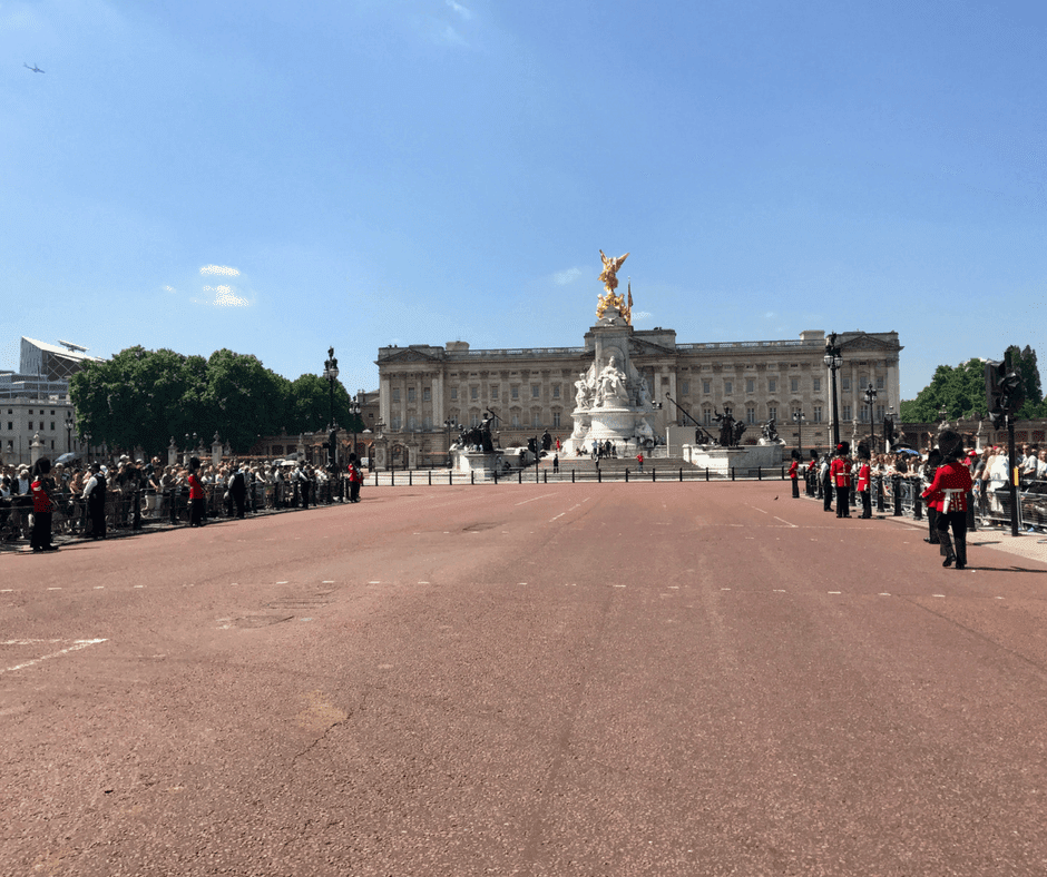 People line streets outside Buckingham Palace. The roads are clear.