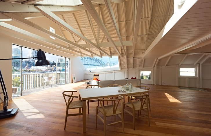 Wooden dining table in Lavender Bay Boatshed by Stephen Collier Architects