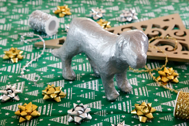 Metallic silver painted dog ornament with Christmas decorations