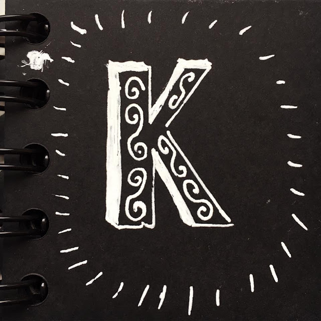 Letter K with decorative elements. Drawn with white ink on black paper. By Boriana Giormova