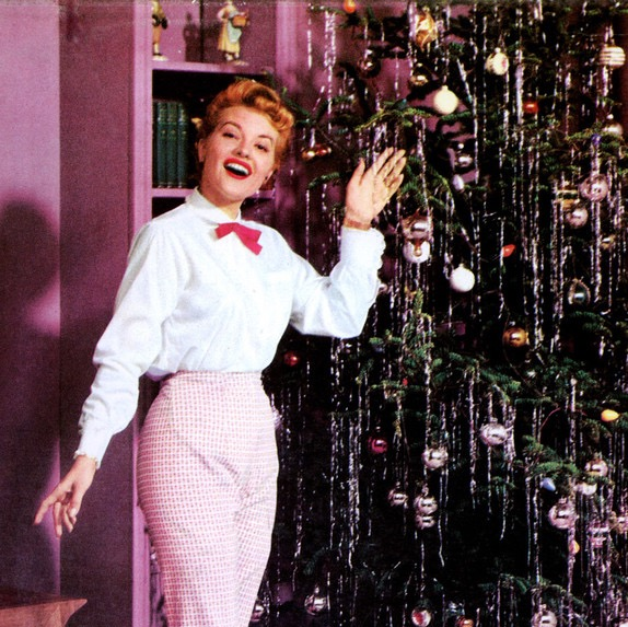woman singing near the christmas tree in what looks like the 50's, power songs, empowering songs for girls