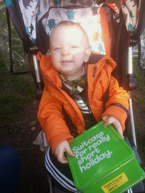 little boy in pram holding lunchbox