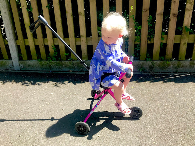 A toddler on a pink Micro trike