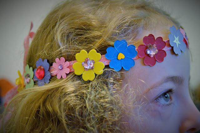 Girl with curly hair wearing hair wreath.
