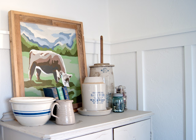 Farmhouse Master Bedroom Reveal - Benjamin Moore Simply White, Paint by number cow painting . antique crocks, red wing, chicken feeder, books, mason jars