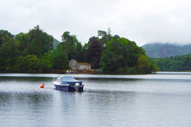 a small boat out on derwent water with an island in the background
