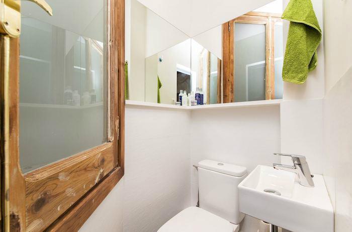 Baño muy pequeño con espejo en escuadra.