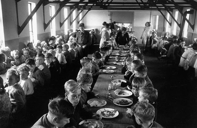 An overcrowded dining hall at Walsgrave Colliery School near Coventry, England filled by children of the post war baby boom, 1952.