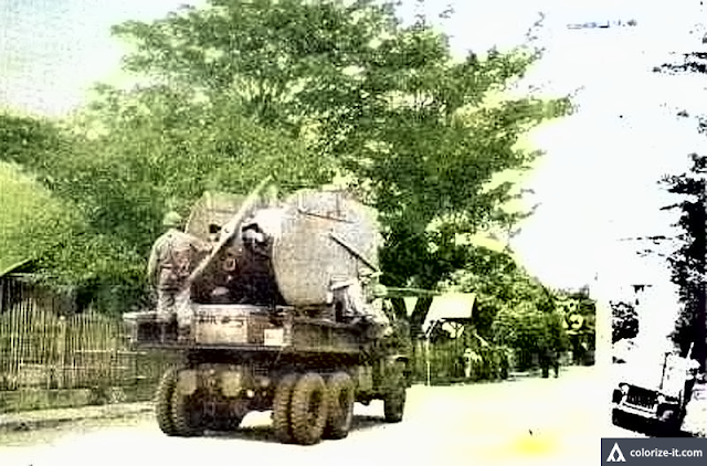 A light plane being carried on a truck through a street in Nasugbu, 1945. Image source:  Eyes Of The War: A Photographic Report Of World War II, Vol. II.  Colorized courtesy of Algorithmia.