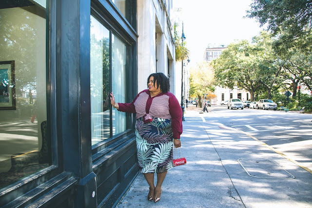 Kirsten is standing in the street in Savannah, Georgia.  She is looking into the window of a business and smiling while holding a sparkly CocaCola clutch bag.  She is wearing a burgundy top, floral skirt rose gold shoes.