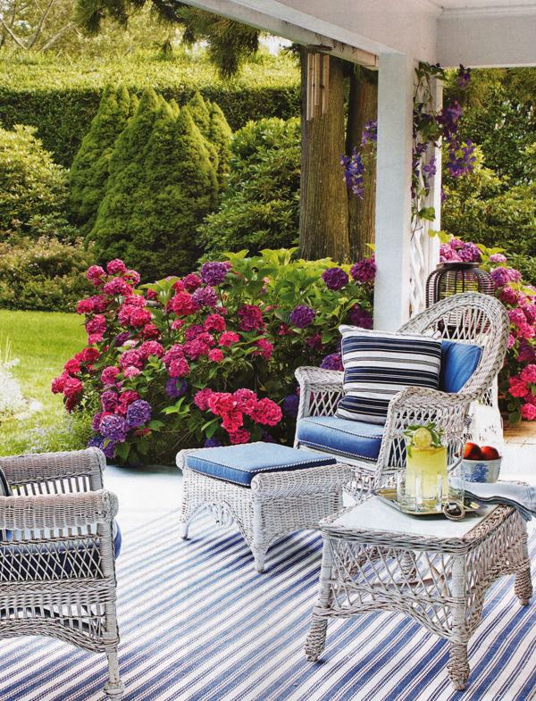 White Wicker Furniture Patio with Blue and White Rug and Hydrangea