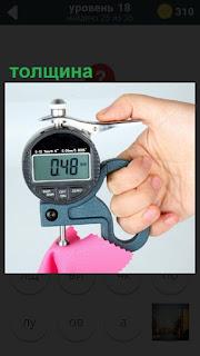 Измерение микрометром толщины материала и показывает значение в числах