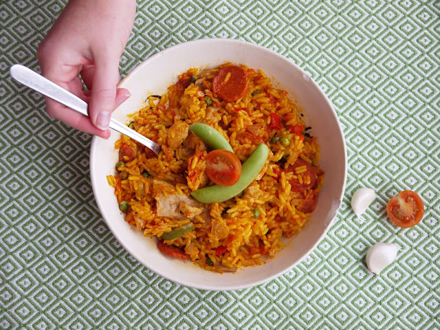 a bowl of iceland vegan paella with a hand and fork reaching in
