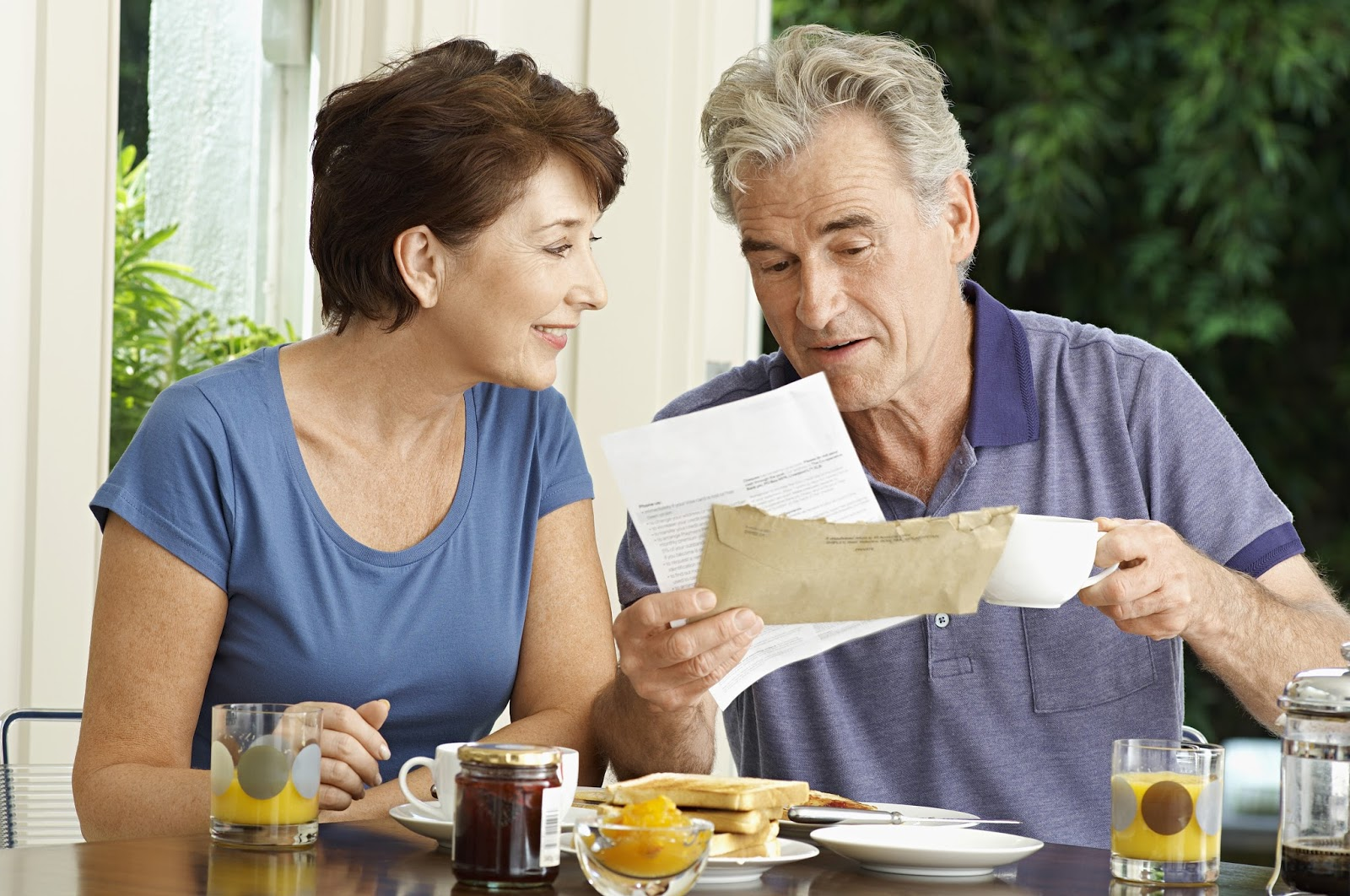 Older man & woman discussing something over breakfast