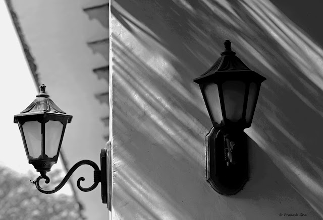 A Looking-up Black and White Minimalist Photo of Two Lamps, one of them being covered with Shadow.