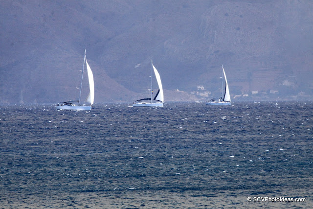 Three sailboats in the horizon