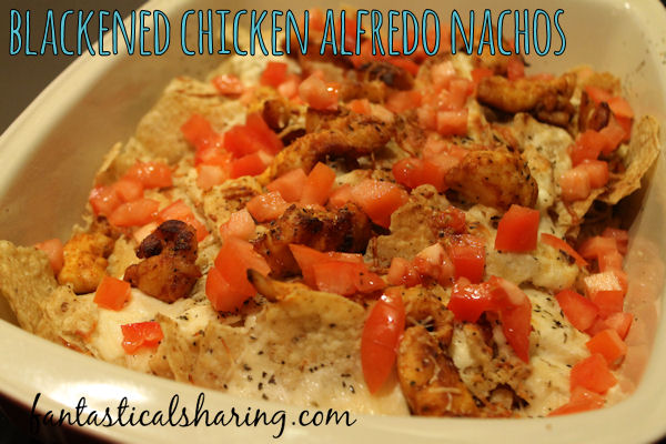 Blackened Chicken Alfredo Nachos // These untraditional nachos are topped with spice-crusted chicken, creamy alfredo sauce, and juicy tomatoes #nachos #chicken #alfredo #maindish