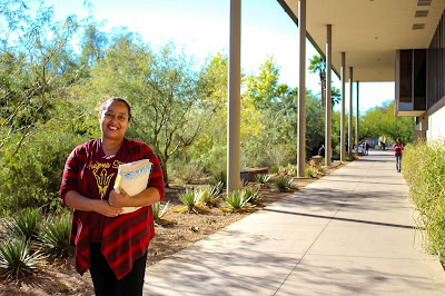 Photo of Tiffany Thornhill - Glendale Community College student holding documents under a walkway with plants and shrubbery in background