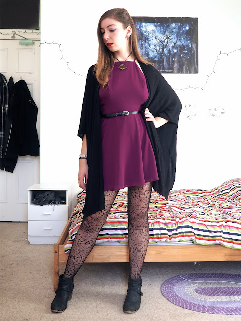 Evil Queen Disneybound villain outfit of bright purple dress, black cape cardigan, spider web tights and black ankle boots