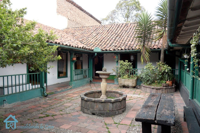 old colonial house with terracotta roof and a patio in its center with a fountain surrounded by railing.