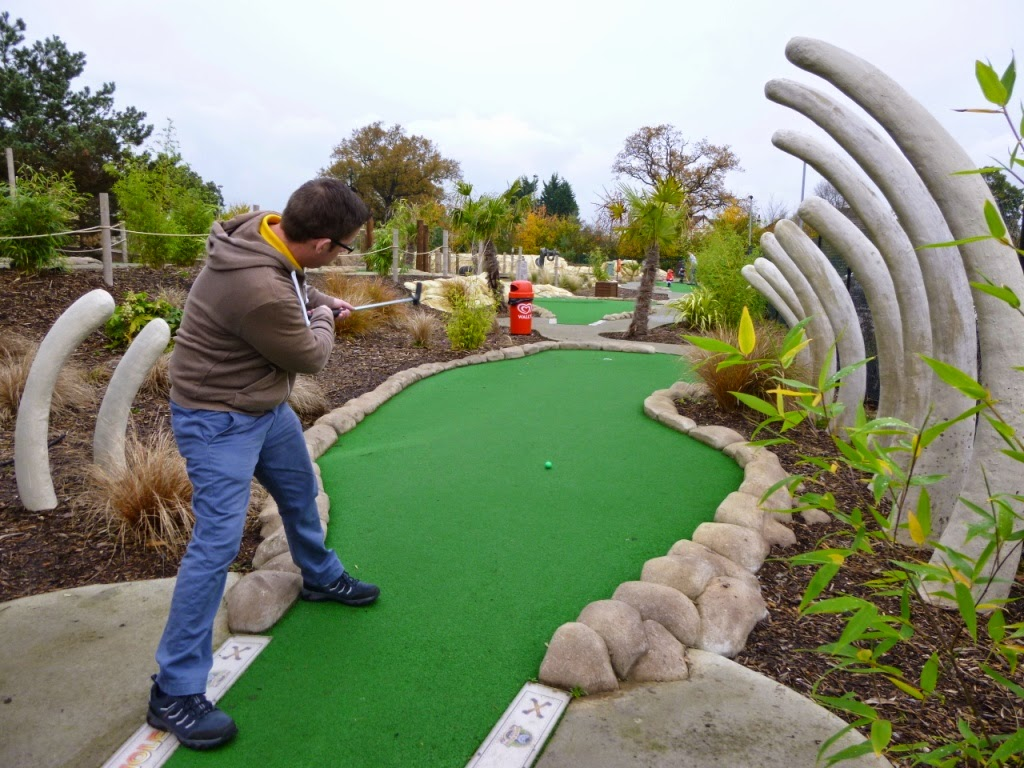 'Squire' Richard Gottfried putts through the remnants of a dinosaur at the Jungle Island Adventure Golf course in Epsom, Surrey