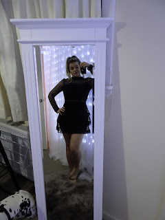 woman in black peplum dress posing in white full length mirror