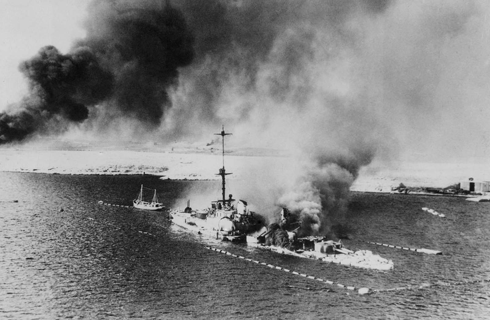 This photo, made from a British warplane during the assault of Tobruk shows the Italian Cruiser San Giorgio, burning amidships, in the harbor of Tobruk, on February 18, 1941. The ship was scuttled, its decks appear to be covered with wrecked and smashed gear.