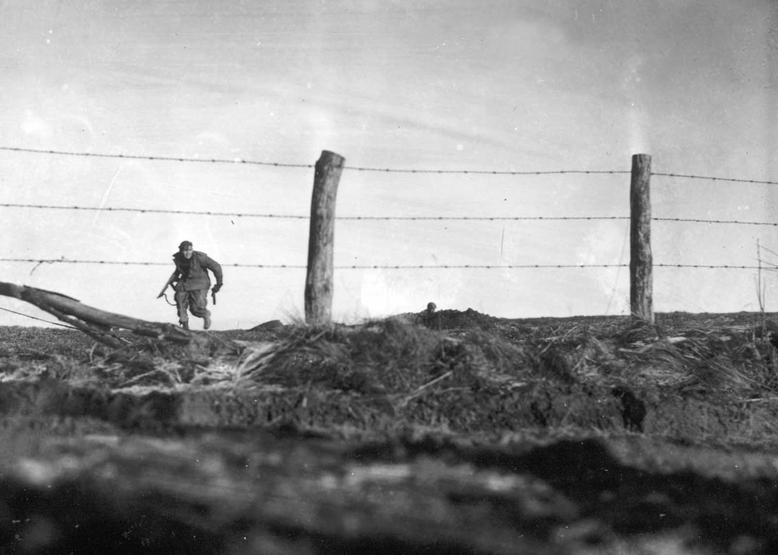 An infantryman from the U.S. Army's 82nd Airborne Division goes out on a one-man sortie while covered by a comrade in the background, near Bra, Belgium, on December 24, 1944.