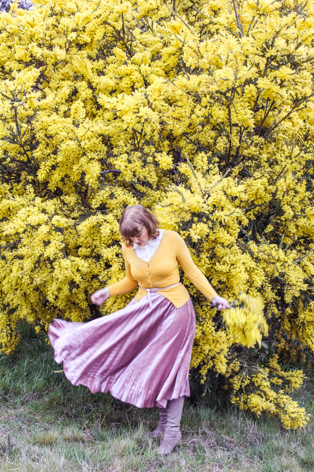 Liana of @findingfemme in pink velvet pleated skirt and mustard cardi
