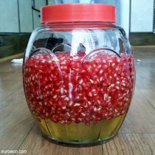 Frasco con lóculos de granada mezclados con miel
