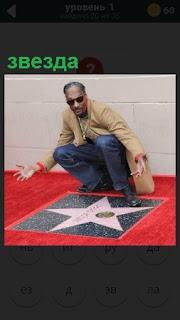 мужчина знаменитость осматривает свою звезду на тротуаре в его честь