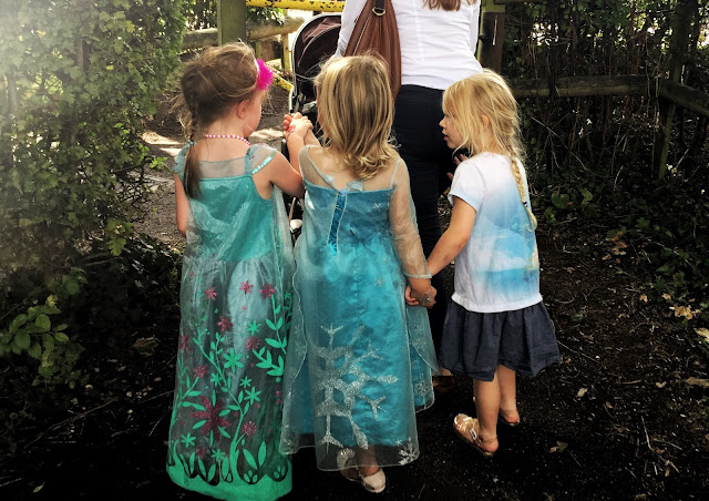 3 young girls in Frozen style dresses walking along holding hands and talking