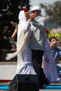 Un chulapo y y una chulapa con sus trajes típicos bailan agarrados
