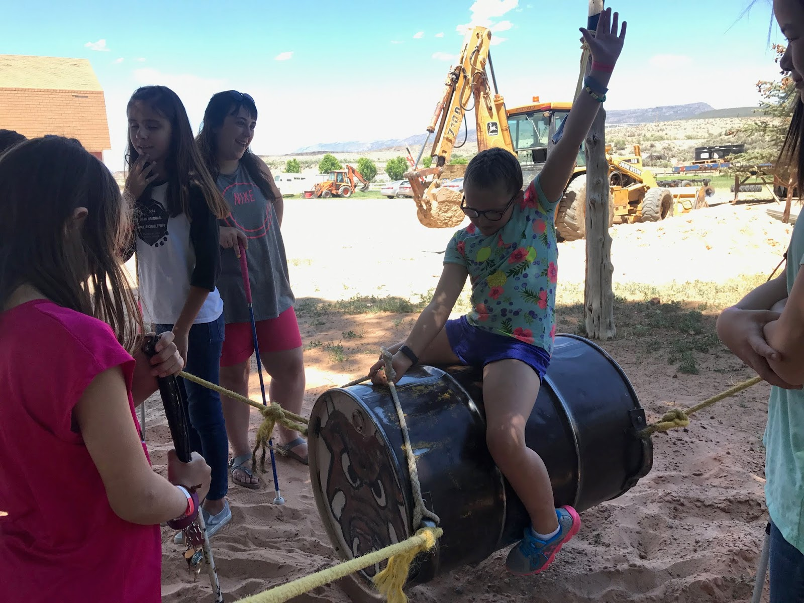 a female student is on a barrel to simulate riding a bull while other students pull attached cords at the corners of the barrel for the simulation