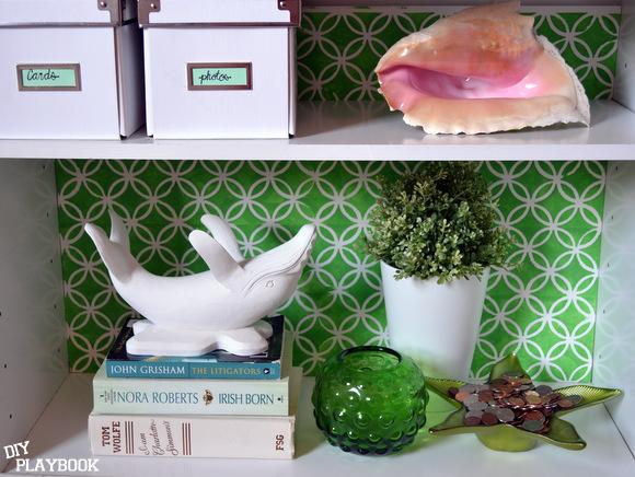 White wooden whale on green bookshelf decor