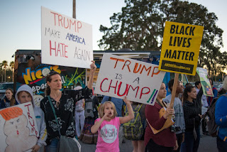 Protesters hold signs during the Trump visit to USF Tampa, FL.