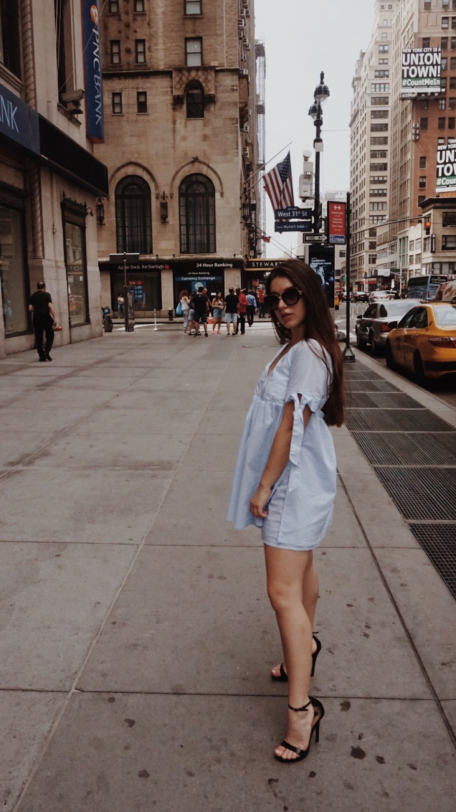 Girl standing on the street in front of Stewart Hotel NYC