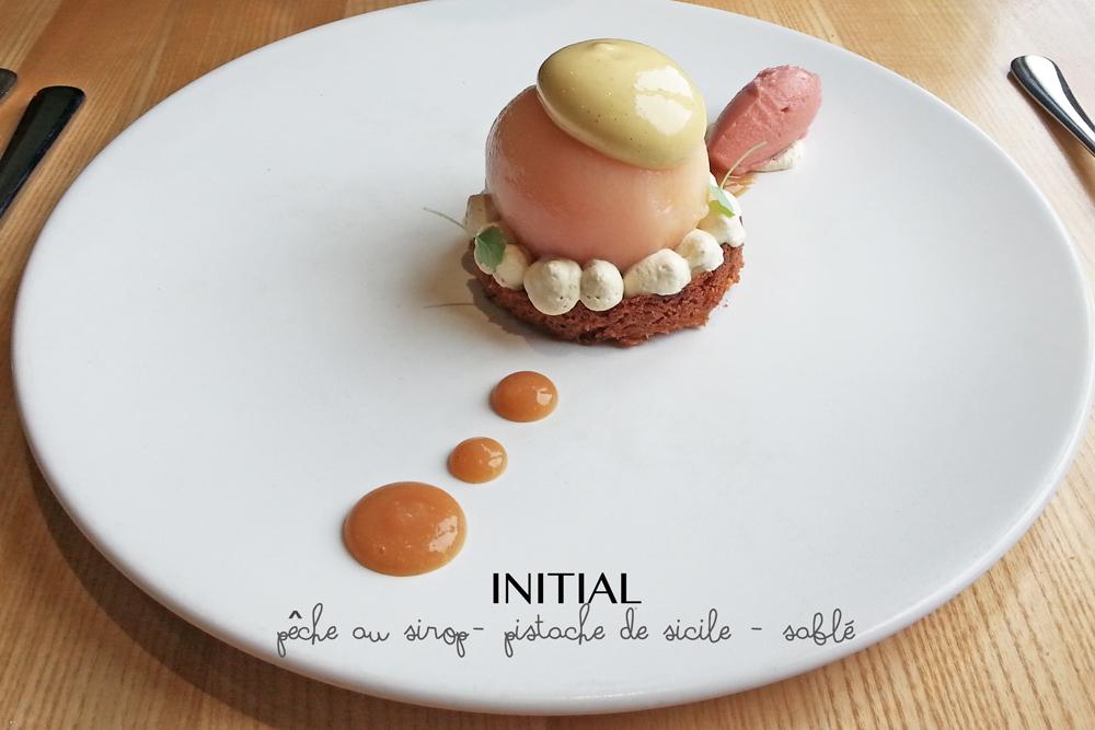 Dessert du Restaurant Initial Caen composé d'une pêche au sirop à la pistache de Sicile sur un sablé
