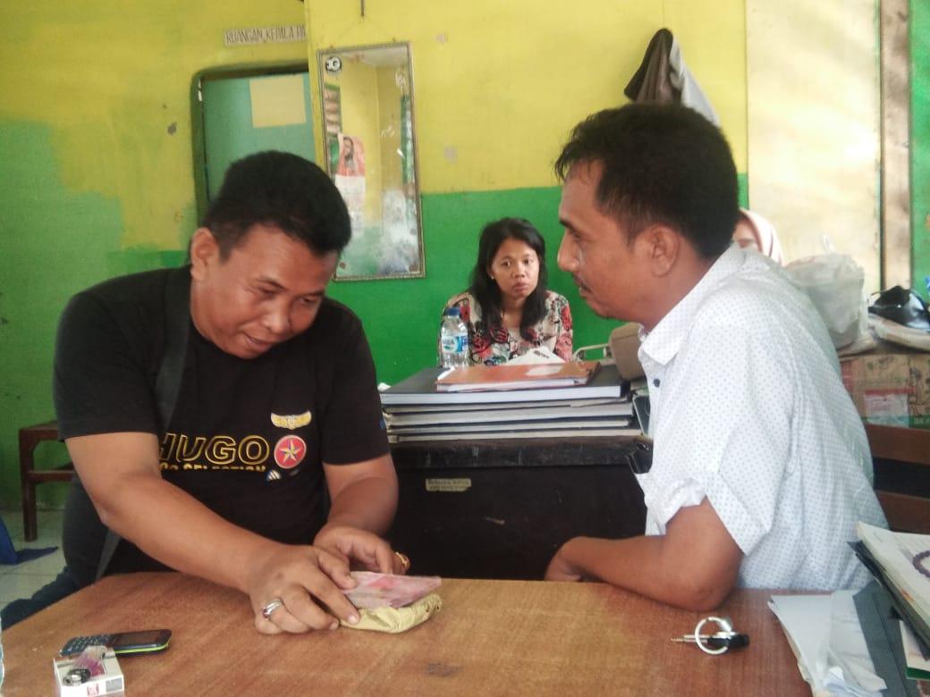 SETOR: Budi S saat menyetor iuran bulanan kepadaKepala Pasar Kwala Bekala/Pasar Inpres, M Prananta Ginting SH