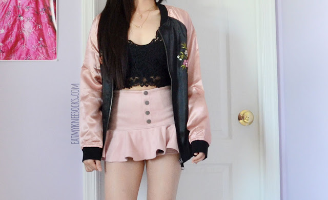 A cute pastel outfit featuring the dusty pink and black floral embroidered oversized satin bomber jacket from SheIn, paired with spiked Jeffrey Campbell Lita dupe platform booties, a Japanese faux suede baby pink buttoned skort, and a black lace cropped bralette.