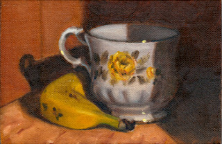 Oil painting of a banana beside a bone china teacup with a yellow rose-pattern.