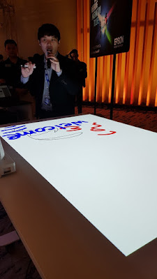 Placing a projector on one side of a folding table allows students to crowd round and interact with the screen.