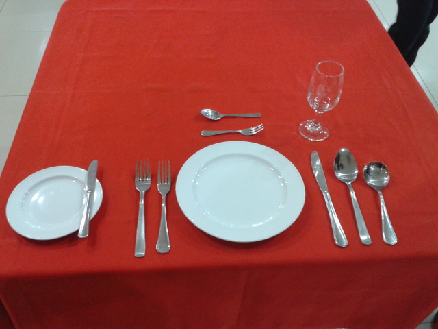 banquet coordinator setting cutlery on table