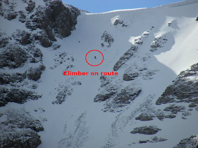 A climber on a steep snow-covered mountainside