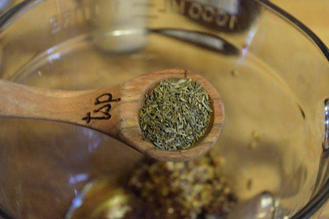 A teaspoon of dried thyme being added to the mixing bowl.
